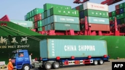 Click to enlarge--A truck transporting a container leaves the port of Qingdao, in northeast China.