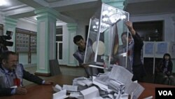 Panitia pemilu di Kirgistan menuangkan surat suara untuk dihitung. Perolehan sementara tidak menunjukkan ada pemenang mutlak.