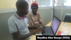"""Ibrahima Kane et Serigne Saliou Ndiaye (à gauche) en plein """" codage"""" dans leurs bureaux de l'Ecole supérieure polytechnique de Dakar, le 29 avril 2017. (VOA/Seydina Aba Gueye)"""