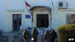 Tentara Rusia memasuki markas besar batalion marinir Ukraina untuk mendiskusikan penyerahan diri mereka di kota Feodosia, Krimea (23/3).
