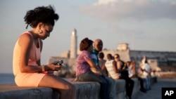 Kubanka koristi mobilni telefon na šetalištu Malekon u Havani, 11. marta 2014.