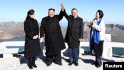 South Korean President Moon Jae-in and North Korean leader Kim Jong Un pose for photographs on the top of Mt. Paektu, North Korea, Sept. 20, 2018.