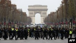 Polisi anti huru-hara Perancis menghadang para demonstran berjaket kuning (gilets jaunes) yang berunjuk rasa memprotes kenaikan harga BBM di Champs-Elysees, Paris, 15 Desember 2018. (Foto: dok).
