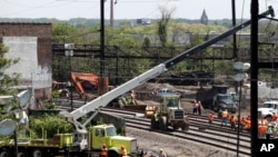 Workers labor at the site of Tuesday's derailment of an Amtrak Northeast Regional train in Philadelphia, May 15, 2015.