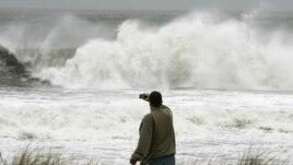 Yon nèg ap pran foto gwo lanm-lanmè siklòn Sandy kòmanse pwovoke nan vil Ocean City, nan Eta New Jersey.