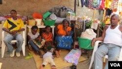 Familia de Alves Kamolingue, com a esposa sentada no chão, à esquerda e o filho no chão a dormir (VOA / Coque Mukuta)