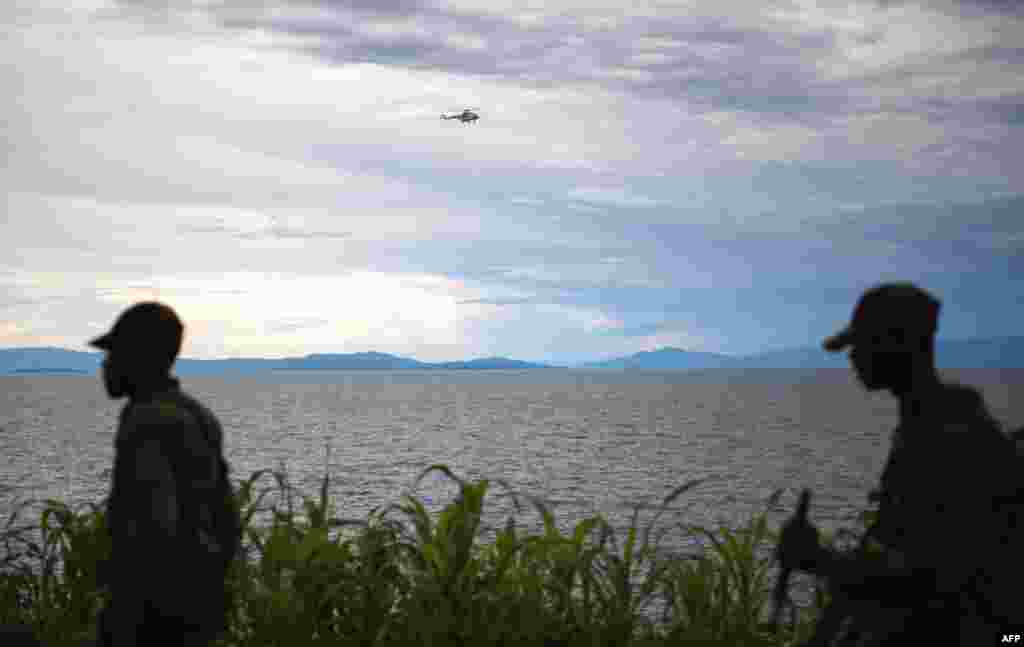 A United Nations helicopter flies over Lake Kivu as M23 rebels walk along the shore in the city of Goma, November 20, 2012.