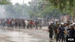Polisi Bangladesh di Asulia melarikan diri dari amukan ribuan buruh garmen yang marah.