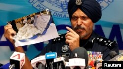 Commissioner Amar Singh, Malaysia's Federal Commercial Crime Investigation Department (CCID) director, displays a photo of items from a raid during a news conference in Kuala Lumpur, June 27, 2018.