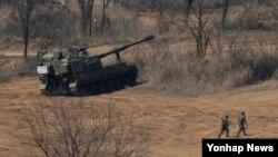 24일 한국 경기도 파주시 접경지역에서 K-9 자주포와 탄약운반차량이 대기하고 있다. 이날 박근혜 대통령은 북한의 위협에 대응해 전국에 경계태세 강화를 지시했다.