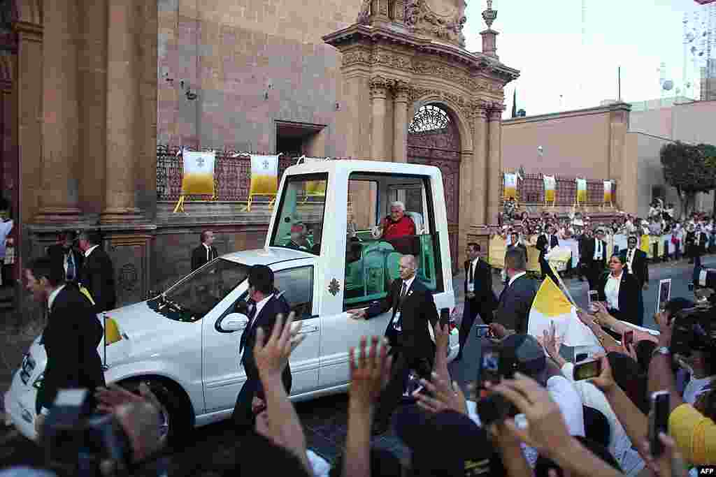 Pope Benedict XVI waves to faithful from his popemobil as arrives for a vespers with bishops of Mexico and the American continent at the cathedral in Leon, Mexico, March 25, 2012. (AP)