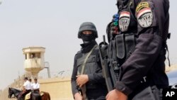 Egyptian policemen secure Egypt's national police academy, where an Egyptian criminal court sentenced ousted Islamist President Mohammed Morsi and 12 Brotherhood leaders and Islamist supporters to 20 years in prison over the killing of protesters in 2012,