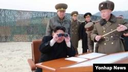 Shimoliy Koreya rahbari Kim Chen Un durbindan raketa uchirish mashqini tomosha qilmoqda, Pxenyan, 2014-yil, 30-dekabr.