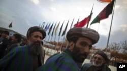 Members of the Loya Jirga, or grand assembly, prepare to leave after its closing ceremony in Kabul, November 19, 2011.