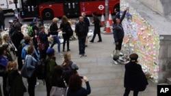 Seorang pria meletakan secarik kertas di antara pesan-pesan untuk memprotes serangan teror di dekat Jembatan London, 8 Juni 2017.