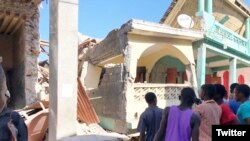 Ljudi stoje ispred srušene zgrade posle zemljotresa u mestu Džeremi na Haitiju, 14. avgusta 2021. TWITTER @JCOMHaiti/ via REUTERS