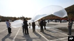 FILE - South Korean activists prepare to release a balloon with leaflets condemning North Korea near Unification Observation Post in Paju, South Korea, October 29, 2012.