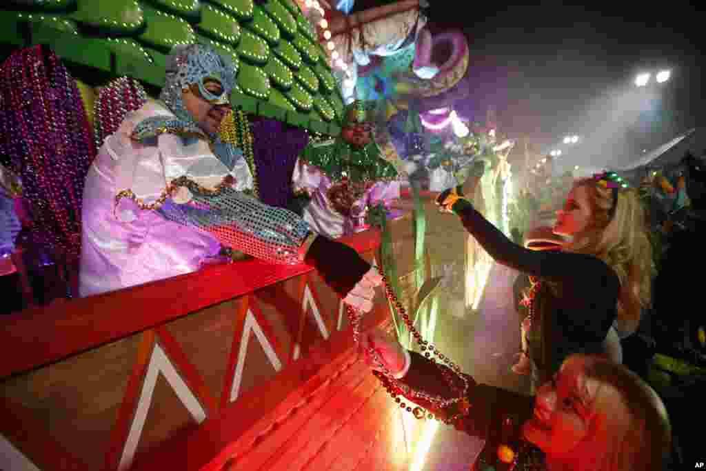 Participantes en las carrozas flotantes regalan collares a la multitud mientras el Krewe of Orpheus avanza en Nueva Orleáns, el lunes 12 de febrero de 2018. Decenas de miles de juerguistas llenan las calles de Nueva Orleans para desfiles y diversión mientras el Mardi Gras cierra la temporada de Carnaval en una ciudad con una celebración propia, su 300 aniversario. (AP Photo / Gerald Herbert)