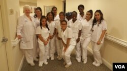 Linda Hall poses with the students in the CNA class. (VOA/F.Elmasry)