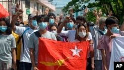 Anti-coup protesters hold the flag of the National League for Democracy party of ousted Myanmar leader Aung San Suu Kyi, while others flash the three-fingered salute during a 'flash mob' rally in Bahan township in Yangon, Myanmar, May 9.