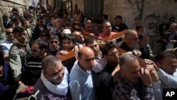 Christian worshipers carry a cross towards the Church of the Holy Sepulcher, traditionally believed by many to be the site of the crucifixion of Jesus Christ, during the Good Friday procession in Jerusalem's Old City, Mar. 29, 2013.