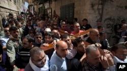 Tín đồ Thiên Chúa Giáo vác cây thập tự gỗ tuần hành qua con phố hẹp của Cổ thành Jerusalem, ngày 29/3/2013.