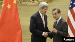 U.S. Secretary of State John Kerry, left, shakes hands with China's Foreign Minister Wang Yi after the met in Beijing earlier this year. Yi is to travel to the U.S. to discuss a number of issues.