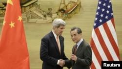 중국을 방문한 존 케리 미국 국무장관(왼쪽)이 27일 베이징에서 왕이 중국 외교부장과 공동기자회견을 마친 후 악수하고 있다.
