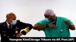 Головний хірург США Джером Адамс (ліворуч) вітає працівника швидкої допомоги Деметріуса Макалістера після того, як Макалістер отримав щеплення вакциною Pfizer від COVID-19