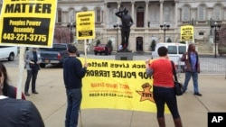 Demonstrators protest the death of Freddie Gray outside Baltimore City Hall, April 20, 2015. Gray died Sunday, a week after he was rushed to the hospital with spinal injuries following an encounter with four Baltimore police officers.