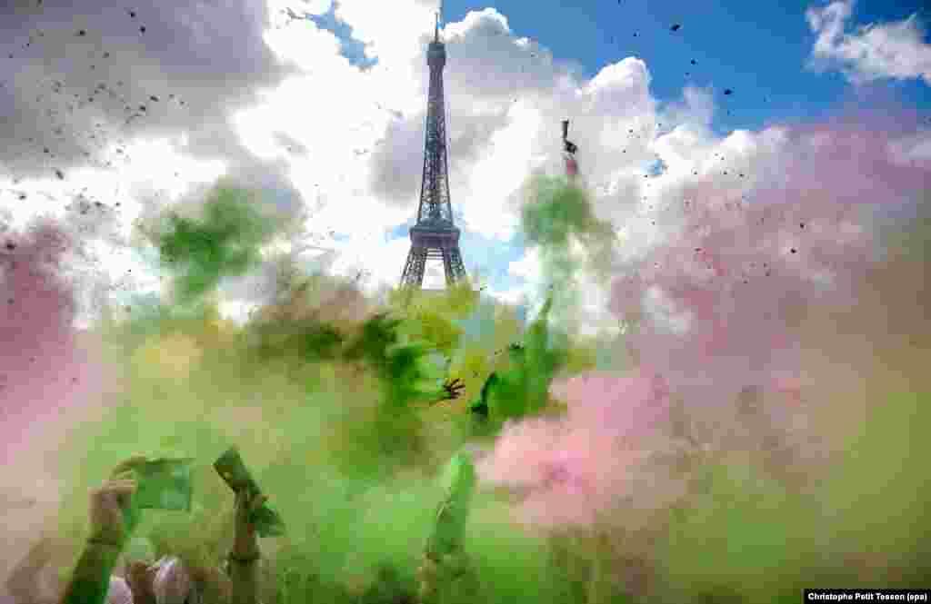 Para peserta melemparkan bubuk warna-warni pada Lomba Lari di Paris, Perancis.