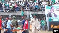 Une femme blessée lors d'une bousculade est emportée sur une civière lors de la cérémonie d'investiture du président de Sierra Leone Maada Bio à Freetown le 12 mai 2018.