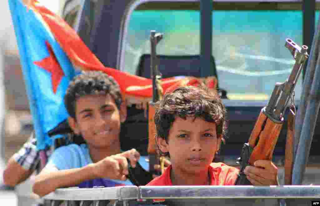 កុមារយេមែនដោយដៃមានកាន់អាវុធ អង្គុយនៅផ្នែកក្រោយឡាន ជាមួយសកម្មប្រយុទ្ធស្មោះត្រង់នឹងប្រធានាធិបតីយេមែនលោក Abedrabbo Mansour Hadi នៅក្នុងសង្កាត់ Dar saad តំបន់ភាគខាងត្បូងនៃទីក្រុង Aden ខណៈពួកគេបន្តការប្រយុទ្ធនឹងក្រុម Shiite Huth ក្នុងប្រទេសយេមែន។