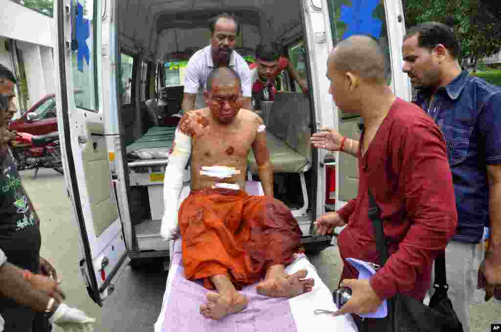 A Buddhist monk is carried on a stretcher for treatment after he was injured in an explosion in Bodh Gaya, Bihar, India, July 7, 2013.