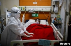 A medical worker takes care of a patient with coronavirus disease, inside the Intensive Care Unit at the Government Institute of Medical Sciences hospital, in Greater Noida, on the outskirts of New Delhi, India, May 21, 2021.