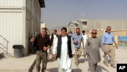 In Afghanistan, a Civilian Response Corps member (left) walks with Kandahar Governor Toorylai Wesa (center). The Corps worked closely with the governor on governance and development issues in Kandahar Province in 2010.