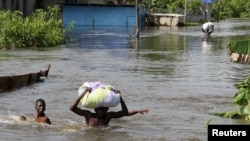 FILE - People wade through a flood with their belongings after their houses were submerged in the Amassoma community in Bayelsa state, Nigeria, Oct. 6, 2012.