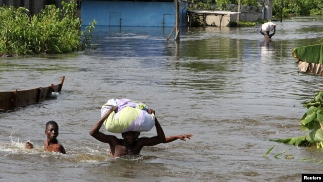People wade through a flood with their belongings after their houses were submerged in the Amassoma community in Bayelsa state, Nigeria, October 6, 2012.