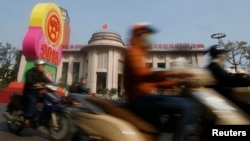 Motorists ride past the State Bank of Vietnam's building in Hanoi December 23, 2014. Vietnam's credit growth is projected to pick up in 2015 to between 13-15 percent to accommodate faster economic growth, compared with 13 percent this year, the central ba