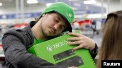 Seorang laki-laki memeluk Xbox One baru, yang dia beli dari Best Buy, 22 November 2017, di Evanston, Illinois.