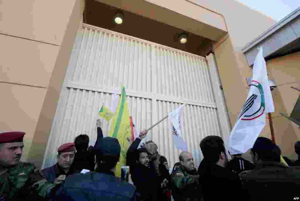 Miembros de las fuerzas de seguridad de Irak tratan de alejar a los manifestantes de la puerta de acceso a la embajada de Estados Unidos en Bagdad (Foto: Ahmad Al-Rubaye/AFP)