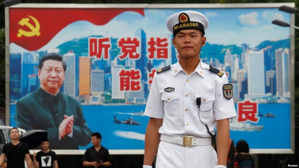 在香港海軍基地,一位中國水兵站在一面具有中共黨旗、習近平像和香港景象的大型看板前面(2017年7月8日)。