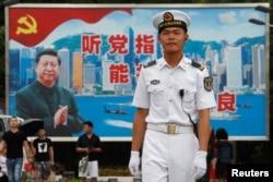在香港海军基地,一位中国水兵站在一面具有中共党旗、习近平像和香港景象的大型看板前面(2017年7月8日)