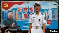 在香港海军基地,一位中国水兵站在一面具有中共党旗、习近平像和香港景象的大型看板前面(2017年7月8日)。