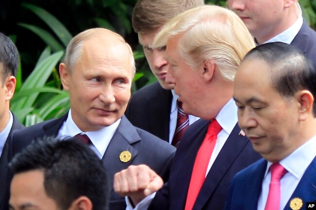 FILE - Russian President Vladimir Putin, left, and U.S. President Donald Trump talk as they arrive for the family photo session during the Asia-Pacific Economic Cooperation (APEC) Summit in Danang, Vietnam, Nov. 11, 2017.