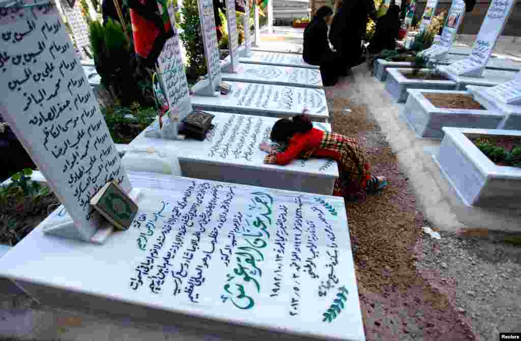 Relatives visit a grave at the Shi'ite fighters cemetery in Damascus, May 28, 2013.