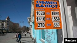 A sign displaying currency rates is seen in Simferopol, Crimea March 22, 2014.