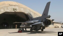 FILE - One of four new U.S.-made F-16 fighter jets outside a hardened hangar upon its arrival to Balad Air Base, north of Baghdad, Iraq, July 2015. Documents and interviews describe schemes at the air base that were major contract violations or illegal.