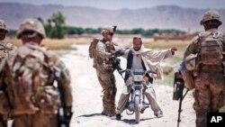 تلاشی یک موتر سایکل سوار توسط سربازان