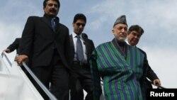 ປະທານາທິບໍດີອັຟການີສຖານ, ທ່ານ Hamid Karzai (ທາງໜ້າ) ພ້ອມຜູ້ອາລັກຂາທ່ານ ຍ່າງລົງຈາກເຮືອບິນ ຢູ່ຄ້າຍທະຫານ Rawalpindi REUTERS/Mian Khursheed (PAKISTAN - Tags: POLITICS)